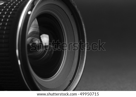 Close-up view of a camera lens from the side with a black background