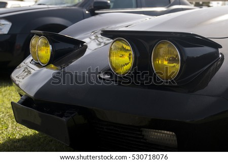 Close up view of a classic car yellow headlights.