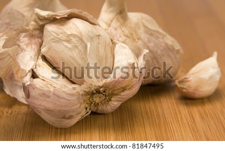 Close up view of a clove of garlic on a wood chopping block.