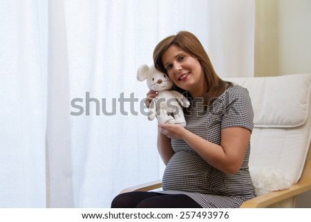 Close up view of a expecting pregnant happy woman holding a stuffed toy. - stock photo