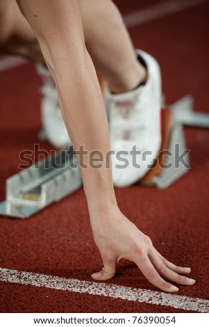 Close up view of a female sprinter ready to go - stock photo