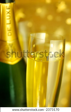 Close-up view of a flute glass and a bottle of Champagne on golden starry background, selective focus on the glass, shallow DOF - stock photo