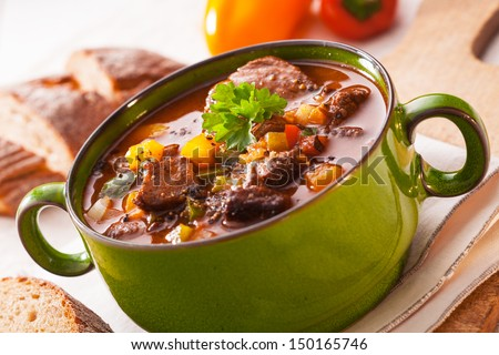 Close up view of a green metal pot filled with a tasty rich meaty stew with vegetables served with sliced baguette - stock photo