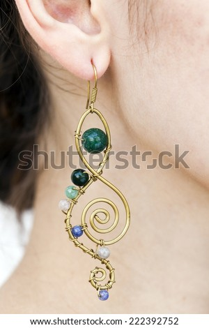 Close up view of a hand made tribal ethnic earing on a woman's ear. - stock photo