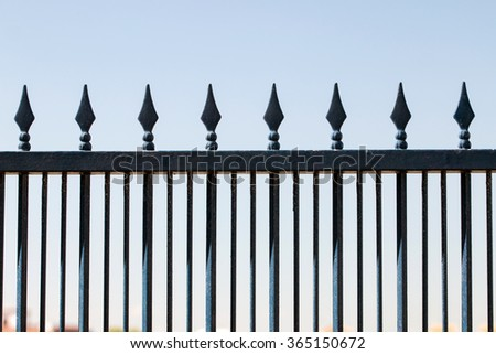 Close up view of a iron forged fence over a blue sky