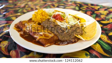 Close up view of a Mexican prepared meal with enchilada, refried beans, yellow rice, and taco. - stock photo