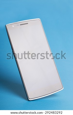 Close up view of a modern thin mobile cellphone isolated in blue background. - stock photo