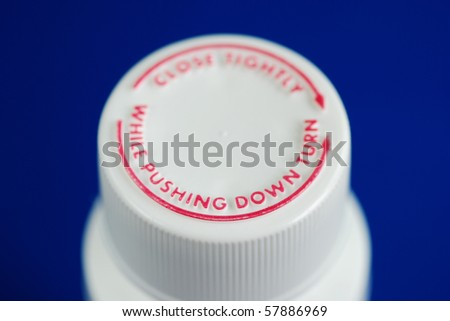 Close up view of a safety caps of a child-proof pill bottle isolated on blue