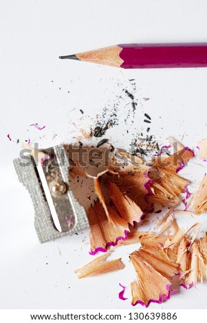 Close up view of a sharpened pink pencil  and a metallic pencil sharpener with wood shavings around them on a desk. - stock photo