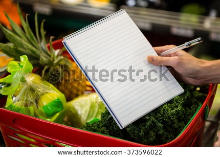 Close up view of a shopping list against a full basket - stock photo