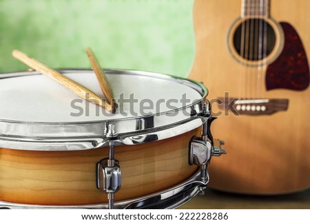 Close-up view of a snare drum and acoustic guitar on a green background - stock photo
