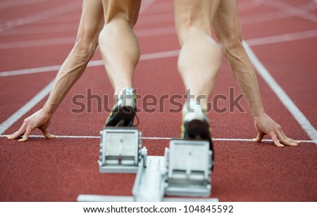 Close up view of a sprinter wearing sprinting shoes with spikes, leaving starting blocks. Selective focus.