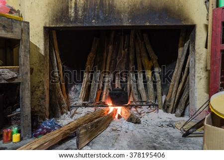 Close-up view of a traditional fireplace/kitchen with bunch of burning firewood to boil water in the old aluminum kettle. This ancient cooking way is still retain in many countryside of Viet Nam.
