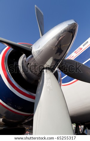 Close up view of a  Vintage Propeller Passenger Airplane with a clear blue sky. - stock photo