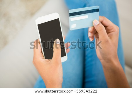 Close up view of a woman holding card and smartphone at home