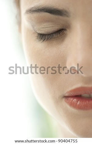 Close up view of a woman's half face with eyes shut.