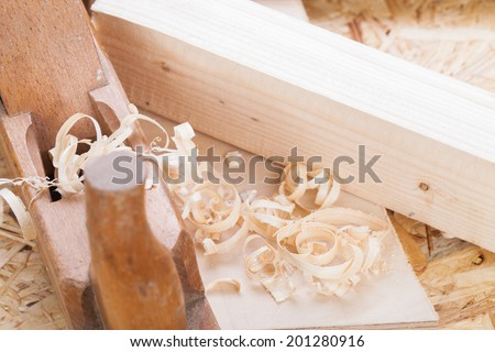 Close up view of a wooden handheld wood plane used to smooth and level the surface of a plank of wood surrounded with fresh wood shavings in a DIY, woodworking, carpentry or joinery concept - stock photo
