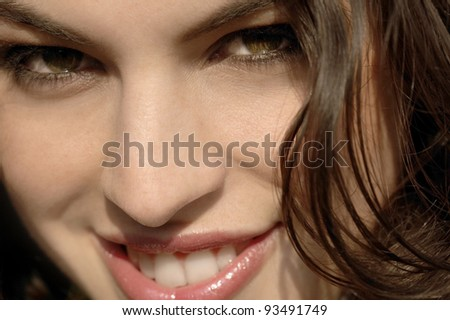 Close up view of a young woman's face smiling and looking at the camera. - stock photo