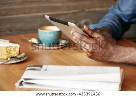 Close up view of African man's hands holding digital tablet, typing a message via social networks. Young black freelancer using electronic device for distance work while sitting at a cozy cafe. - stock photo