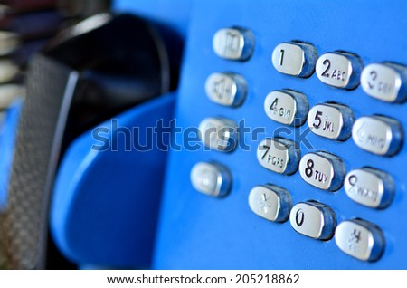 Close-up view of an aging pay telephone with pushbuttons in shallow focus.