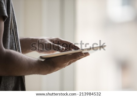Close-up view of an Asian man using digital tablet at home. - stock photo