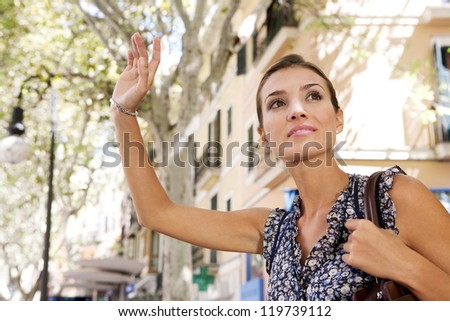 Close up view of an attractive young businesswoman raising her arm to call a taxi in a busy city, outdoors. - stock photo