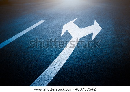 Close-up view of arrow sign on road,blue toned image. - stock photo