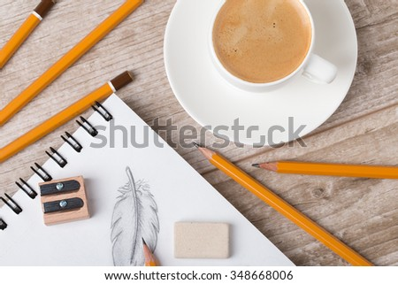 Close-up view of artist's or designer's table. Cup of coffee, pencils, sharpner and eraser laying on sketch book with hand-drawn feathers - stock photo