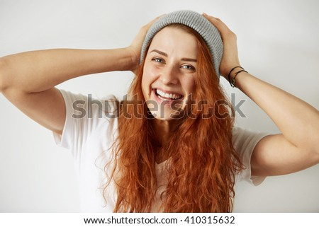 Close up view of attractive young girl with long loose red hair, wearing white T-shirt and gray cap, smiling at the camera, holding her head. Human face expressions and emotions. Selective focus - stock photo