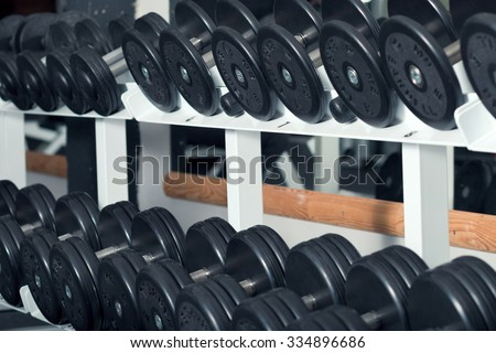 Close-up view of barbells organized in row on rack at gym - stock photo