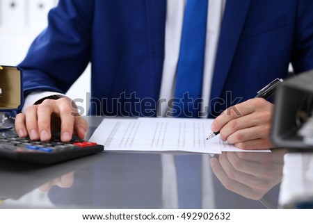 Close up view of bookkeeper or financial inspector hands making report, calculating or checking balance. Internal Revenue Service inspector checking financial document.
