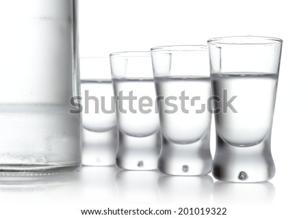 Close-up view of bottle and glasses of vodka isolated on white