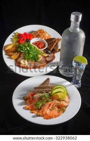 Close-up view of bottle of vodka and glasses with Marinated vegetables and sliced meat  decorated with parsley and dill, also appetizer - salted salmon and bread at the plate standing on black - stock photo