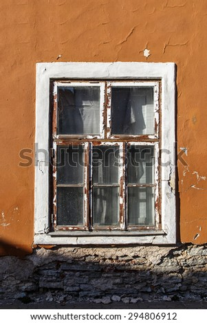 Close up view of brown wooden window of the old orange building. - stock photo