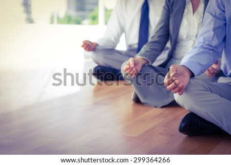 Close up view of business people doing yoga in office - stock photo