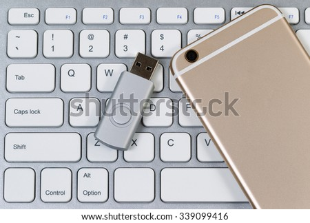 Close up view of cell phone, thumb drive and computer keyboard. Modern mobile technology concept.