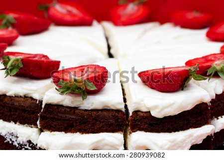Close-up view of chocolate cake with cream and strawberries