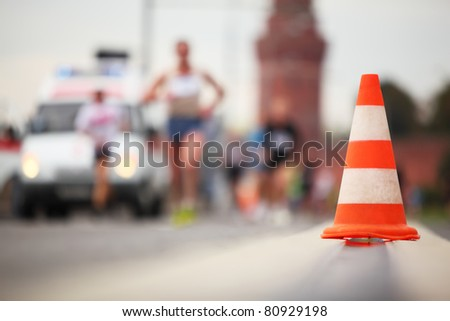 Close-up view of color cone on road on background of running man - stock photo