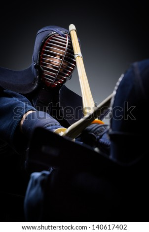 Close up view of competition of two kendo fighters. Japanese martial art of sword fighting - stock photo
