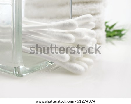 Close up view of cotton swabs and white towels in the background - stock photo