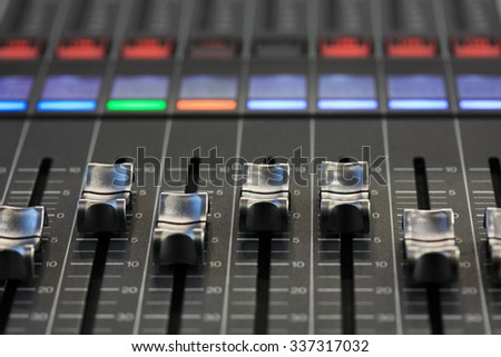 Close up view of digital mixing console. Selective focus on faders. - stock photo