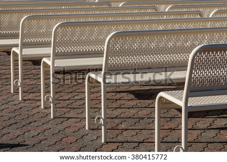 Close-up view of empty benches in rows from behind. - stock photo