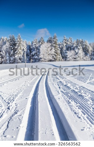 Close-up view of empty cross-country skiing track in beautiful winter wonderland scenery on a sunny day with blue sky with shallow depth of field effect resulting in abstract background blur bokeh  - stock photo