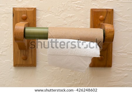 Close up view of end of toilet paper roll showing cardboard roll on wooden holder and half a square of paper.