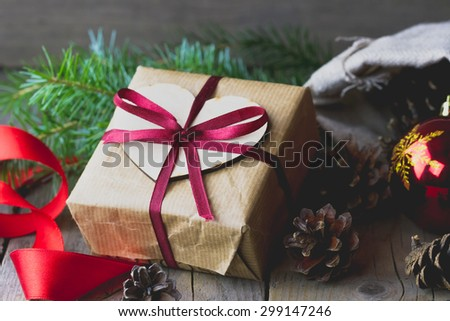 Close-up view of gift box decorated red bow, fur-tree branches, red glass ball and cones on wooden background