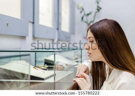 Close up view of girl looking at jewelry in window case at jeweler's shop. Concept of wealth and luxurious life - stock photo