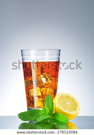 close up view of glass with tea and lemon aside on blue back - stock photo