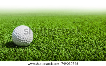 Close-up view of golf ball on the green grass of golf course with white copyspace