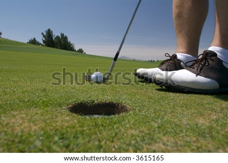 Close up view of golfer putting with hole in foreground - stock photo