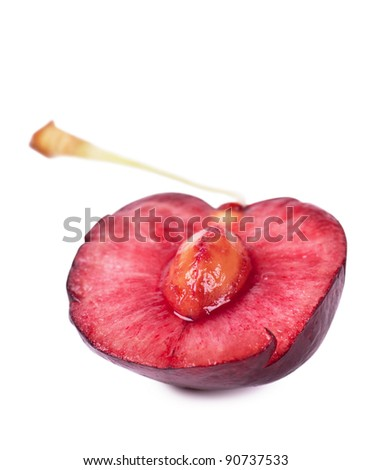 Close up view of half of cherry with kernel over white background with shadow - stock photo